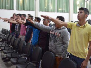 Jovens dispensados do serviço militar fazemjuramentoà Bandeira